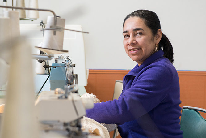 Women enthusiastically learning to sew
